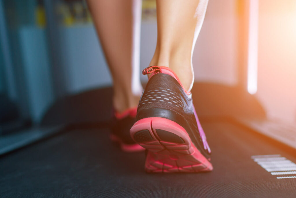 woman's feet walking on treadmill at gym